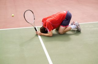 A tennis player crouching on the floor in defeat